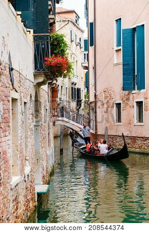 VENICE,ITALY - JULY 26,2017 : Tourists riding a gondola on a small canal surrounded by old buildings in Venice