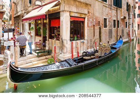 VENICE,ITALY - JULY 26,2017 : Traditional gondola on a narrow canal in Venice