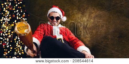 Bad Santa with 2018 baseball bat sitting indoors near Christmas or New Year fir tree