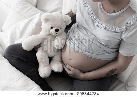 Expectant woman is sitting at bed and stroking belly. She holding teddy bear. Focus on female paunch. Top view