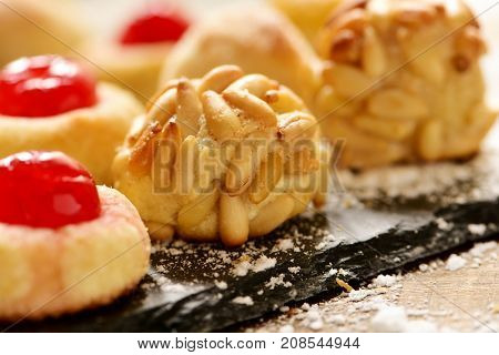 closeup of some panellets, typical confection eaten in All Saints Day in Catalonia, Spain, on a wooden table