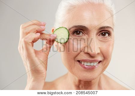 Beauty portrait of a smiling half naked elderly woman holding slice of fresh cucumber at her face and looking at camera isolated over white background