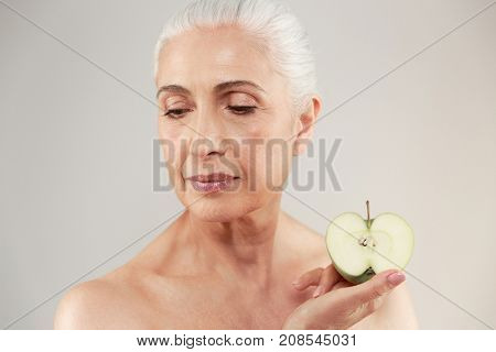Beauty portrait of a beautiful half naked elderly woman holding sliced green apple and looking away isolated over white background