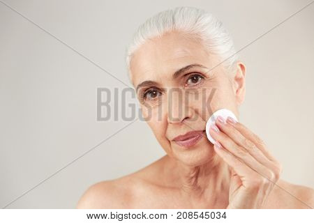 Beauty portrait of a lovely half naked elderly woman removing make-up with a cotton pad isolated over white background