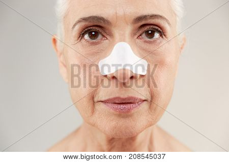 Close up beauty portrait of an old half naked lady with clear-up patches on her nose to remove blackhead looking at camera isolated over white background