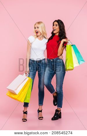 Full length image of two shocked happy women with packages in hands looking away over pink background
