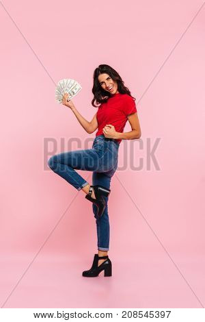 Full length side view image of happy brunette woman rejoice and holding money while looking at the camera over pink background