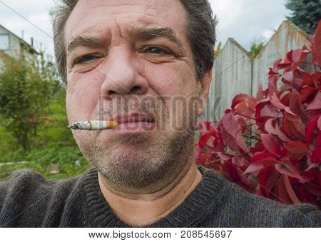 Close-up portrait of an adult smoking man outdoors. Real people
