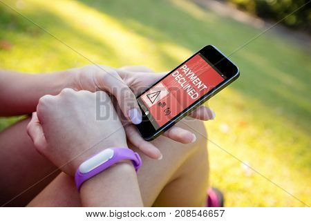 Payment declined text on mobile screen against woman with fitness band on wrist using phone