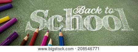 Back to school text against white background against colorful pencils on table
