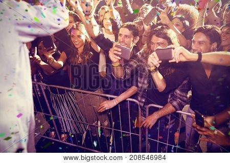 Flying colours against cheerful fans photographing performer at nightclub