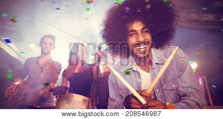 Flying colours against portrait of drummer holding drumsticks at nightclub