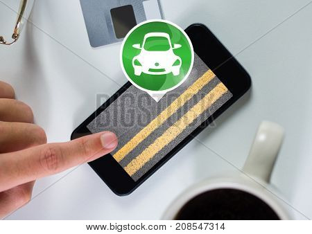 Digital composite of Hand touching phone with car icon with road