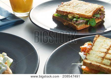 breakfast of eggs, sandwiches and orange juice