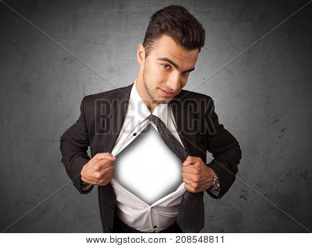 Businessman tearing off his shirt with white copyspace on chest on grungy background