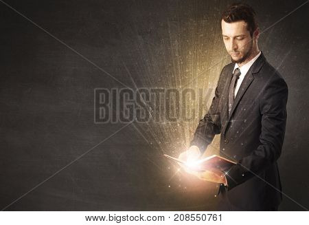 Man holding and reading a shiny book.