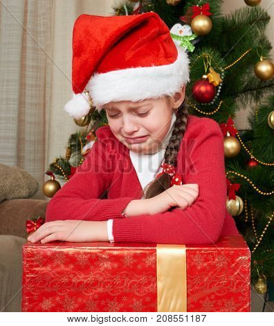 Unhappy girl shed tears near christmas tree, dressed in red and santa hat