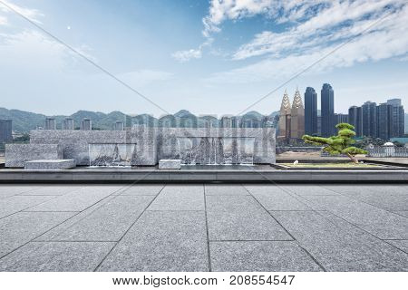 empty marble square with artificial waterfall in blue cloud sky