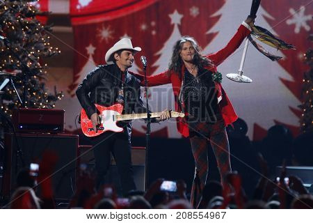 NASHVILLE, TN-NOV 7: Recording artists Brad Paisley (L) and Steven Tyler of Aerosmith perform at the 2014 CMA Country Christmas at the Bridgestone Arena on November 7, 2014 in Nashville, Tennessee.