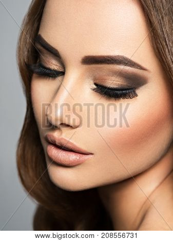 Closeup face of a beautiful  woman  with long eyelashes. Portrait of a pretty young adult girl. Attractive sexy lady posing at studio.