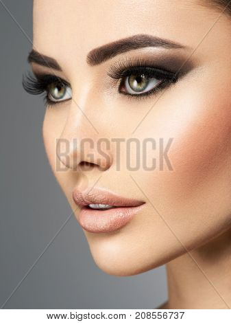 Closeup face of a beautiful  woman  with long eyelashes. Portrait of a pretty young adult girl. Attractive sexy lady posing at studio over grey background.