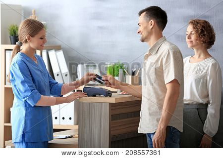 Young female receptionist with clients in hospital