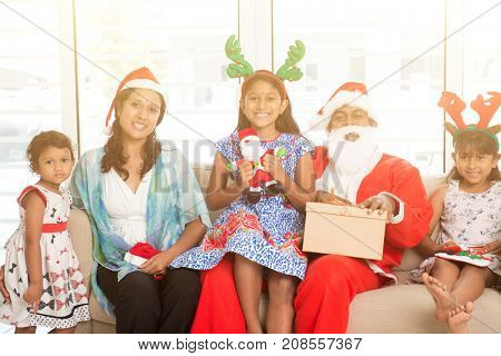 Happy Indian family celebrating Christmas holidays, with gift box and santa sitting on couch at home, Asian parents and children festival mood indoors.