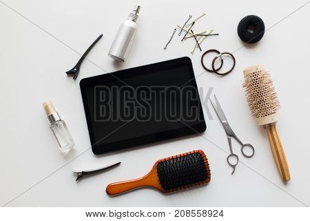 hair tools, beauty and hairdressing concept - tablet pc computer, scissors, brushes and styling sprays with pins and ties on white background