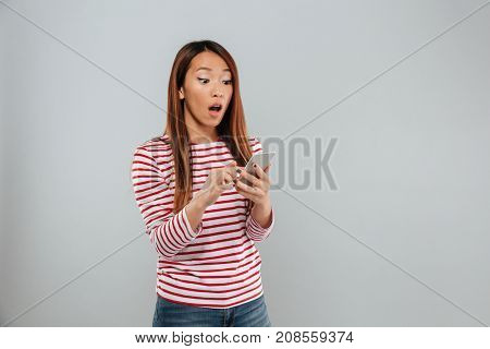 Image of shocked young asian lady chatting by phone standing isolated over grey wall. Looking aside.
