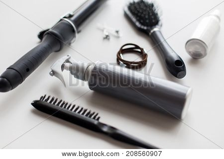 hair tools and hairdressing concept - hot styling spay, curling iron, brushes, ties and pins on white background