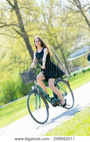 Portrait view of girl on bicycle wearing on black short dress. Young happy Woman riding along road on green spring  outdoor Park. Sporty young girl riding a bicycle on a sunny morning, view from face