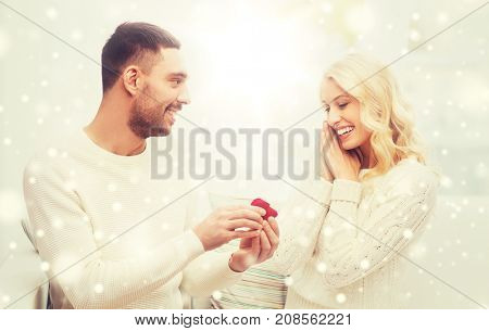 love, christmas, couple, proposal and people concept - happy man giving engagement ring in little red box to woman at home