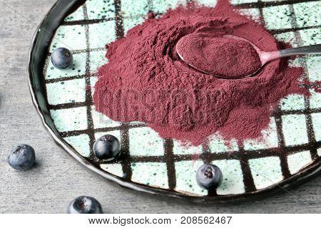 Acai powder, berries and metal spoon on plate