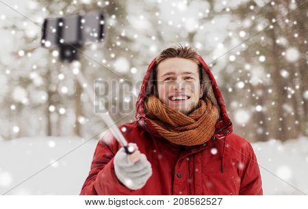 people, christmas, winter and season concept - happy smiling man in hood and scarf taking picture by smartphone selfie stick outdoors