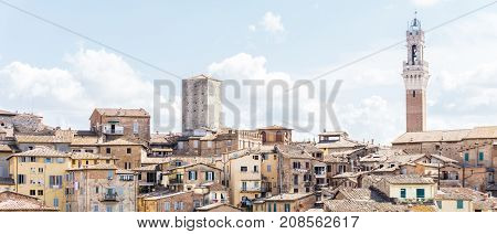 Horizontal photo with view on the town hall tower over the houses and buildings in historic ancient town Siena in Italy Tuscany. The sky is blue with several clouds.