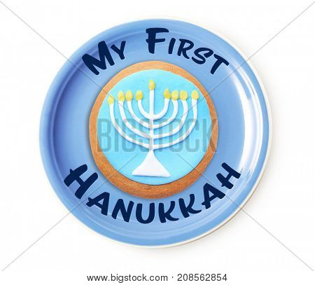 Plate with tasty glazed cookie and text MY FIRST HANUKKAH on white background