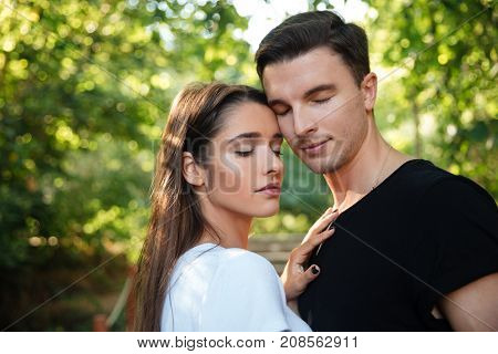 Portrait of a young lovely couple in love standing and embracing at the park outdoors