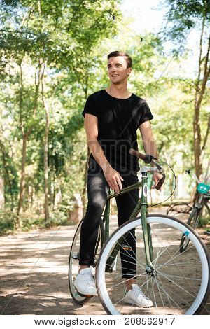 Portrait of a young handsome man riding on a bicycle at a park