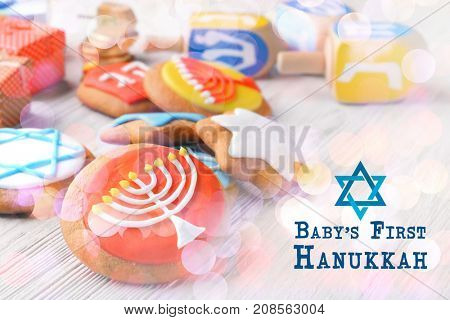 Tasty glazed cookies for baby's first Hanukkah on wooden table