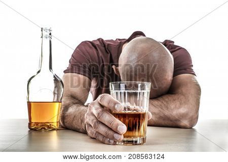 Drunk man with glass and bottle of alcohol drink sitting at table on white background