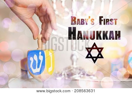 Woman spinning wooden dreidel for baby's first Hanukkah on table