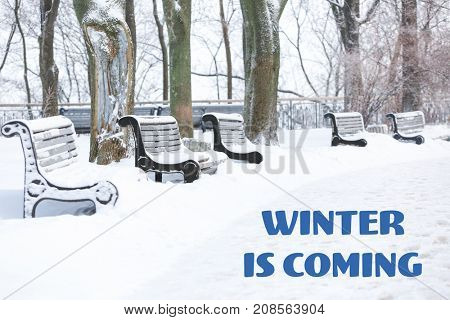 Beautiful view of snowy park and text WINTER IS COMING
