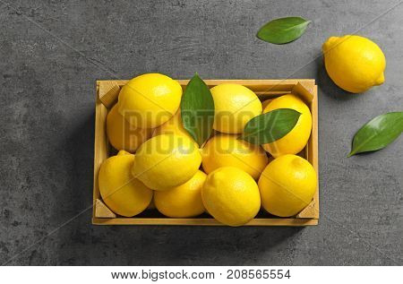 Wooden crate with fresh lemons on table