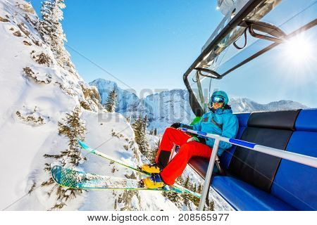 Skier sitting at ski lift in high mountains during sunny day. Winter sport and recreation, leisure outdoor activities.