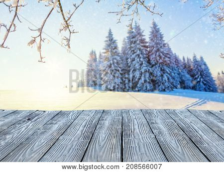 Beautiful snowy landscape panorama with empty old wooden planks, ideal for product placement. Fresh powder snow, winter nature