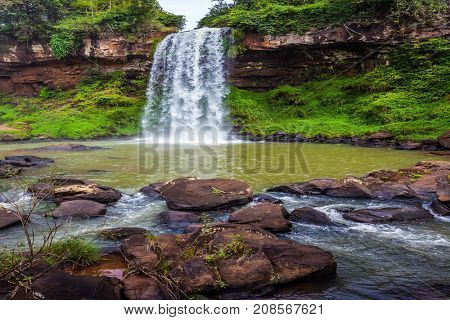 Wide rumbling stream of water falls from the basalt ledge. Travel to Patagonia, Iguazu Falls. The concept of ecological and extreme tourism
