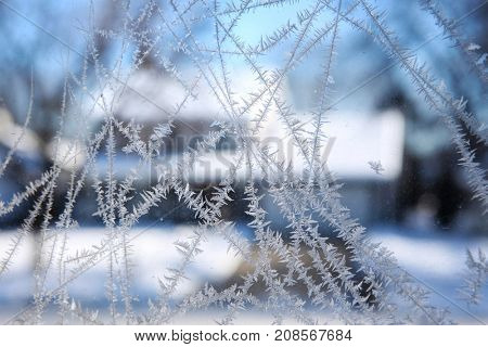 Frost on a window looking out at a winter scene