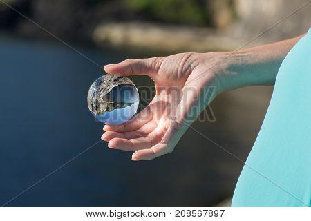 Glass ball in hand, outdoor, sunligh focus on skin, landscape