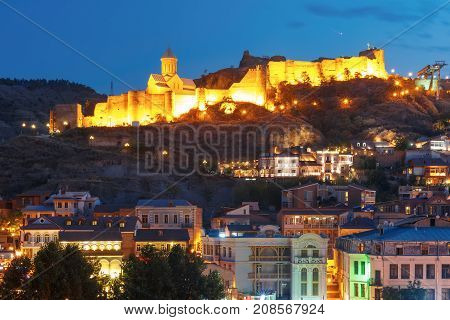 Amazing view of Olt town with Narikala ancient fortress, St Nicholas Church in night Illumination during evening blue hour, Tbilisi, Georgia.