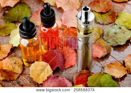 Electronic cigarette or vaping device and assorted vape liquids on wooden table with autumn leaves
